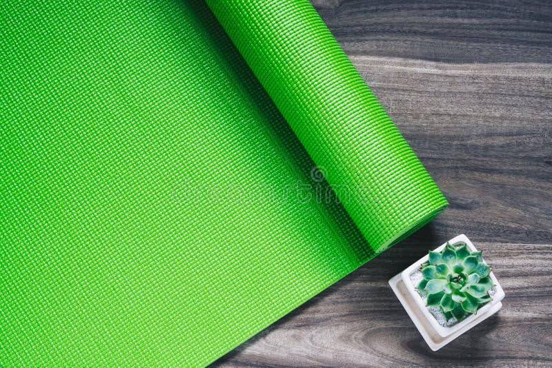 在木背景的绿色瑜伽席子与绿色多汁气喘, 免版税库存照片