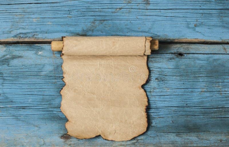 在木背景的羊皮纸纸卷 免版税库存图片