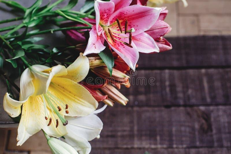 在木背景的美丽的五颜六色的百合花 黄色别针 免版税库存照片
