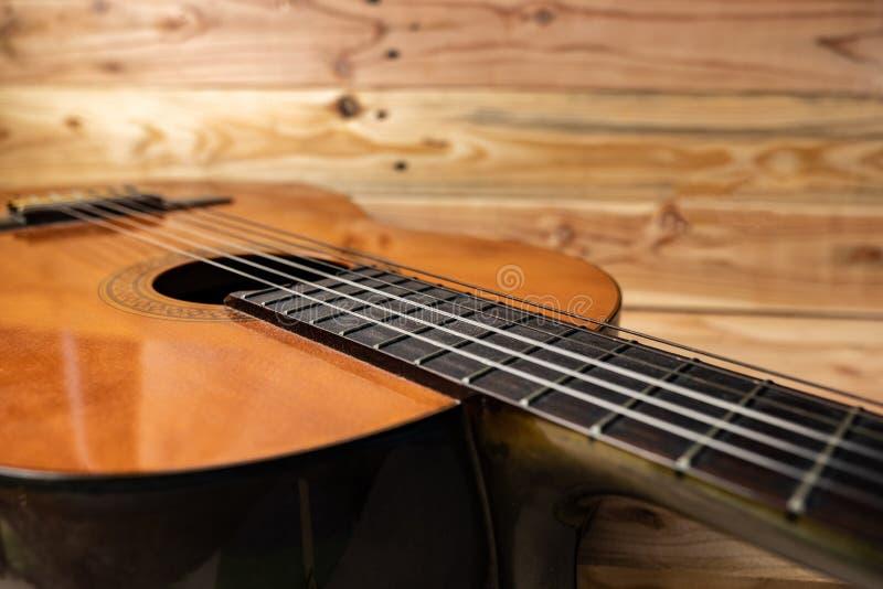 在木背景的老古典吉他 库存图片