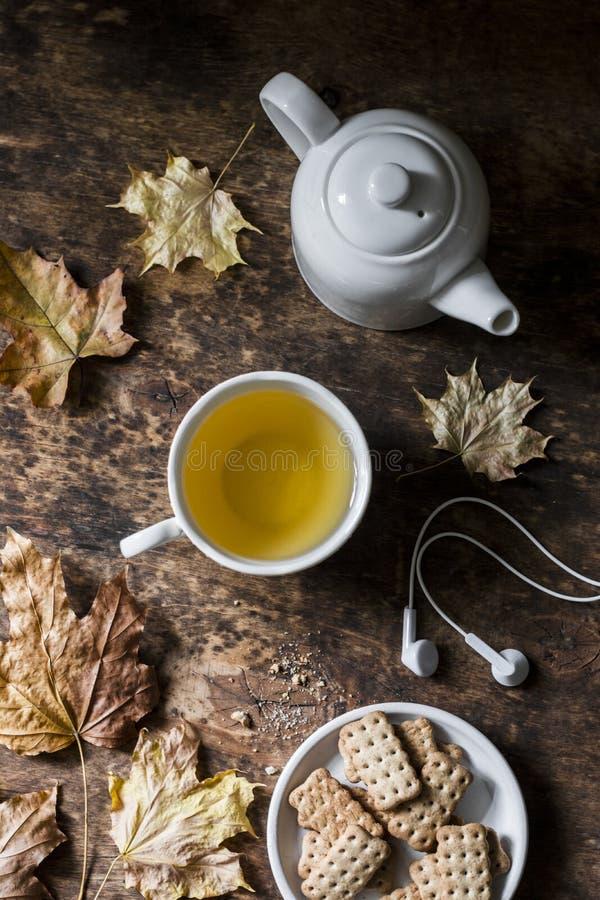 在木背景的舒适秋天静物画-绿茶,整个五谷饼干,耳机,干燥槭树离开 顶视图 免版税库存图片