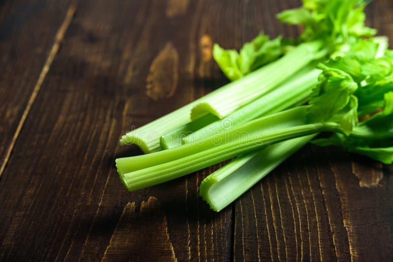 在木背景的芹菜茎 免版税图库摄影