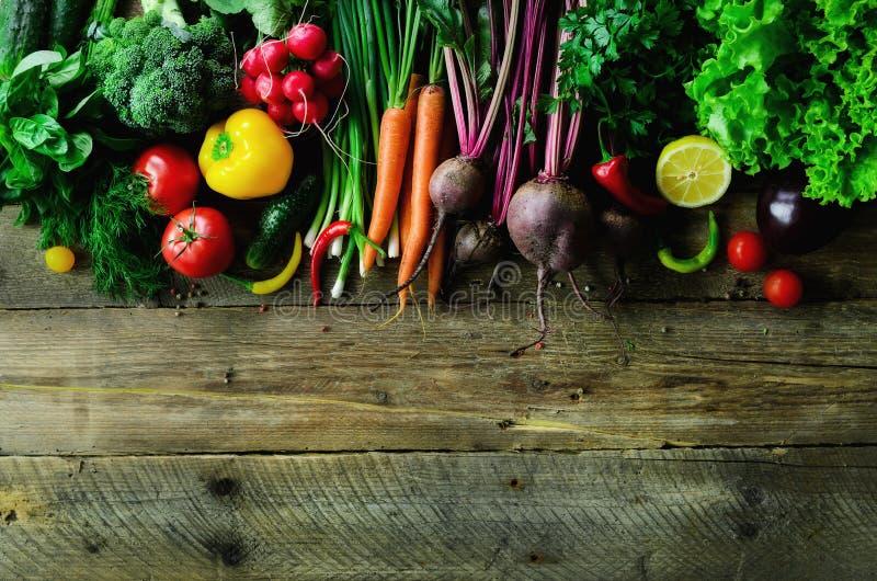 在木背景的菜 生物健康有机食品、草本和香料 未加工和素食概念 成份 免版税库存图片