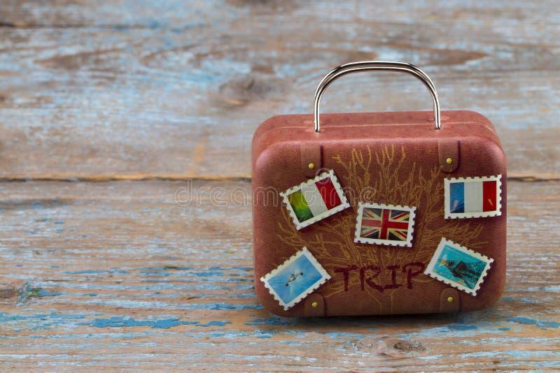 在木背景的葡萄酒经典棕色手提箱 浓缩的旅行 免版税库存照片