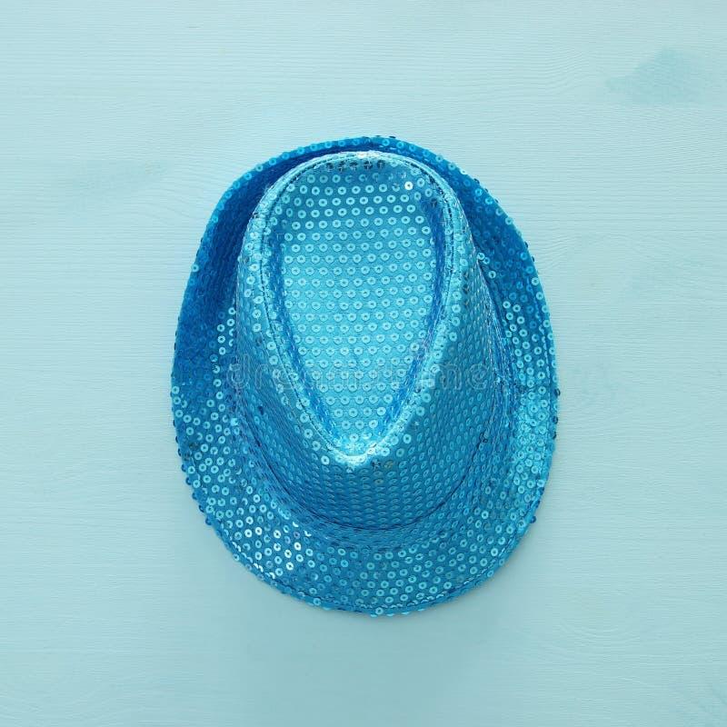 在木背景的蓝色发光的闪光金属片的党帽子 普珥节庆祝概念& x28; 犹太狂欢节holiday& x29; 免版税库存照片