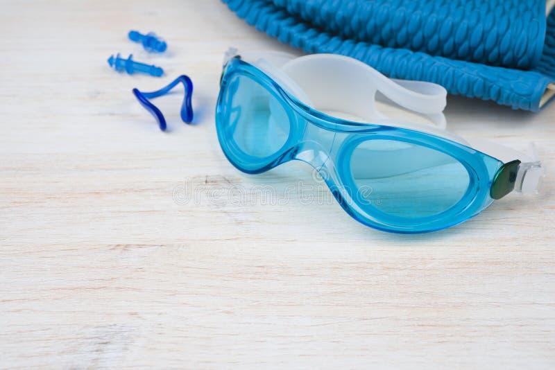 在木背景的蓝色游泳设备 概念查出的体育运动白色 免版税库存图片