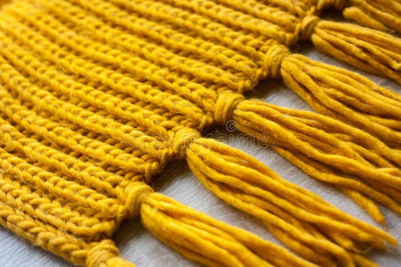在木背景的被编织的黄色围巾纹理 库存照片