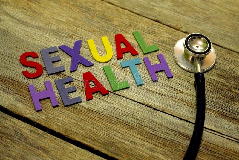 在木背景的词性健康五颜六色的木字母表信件集合和听诊器 医疗保健和医疗概念 免版税图库摄影