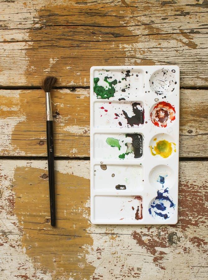 在木背景的调色板和水彩刷子 库存照片