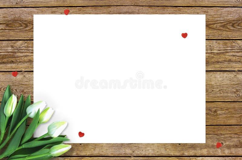 在木背景的郁金香与消息的空间 母亲` s天背景 在土气桌上的花3月8日 库存图片