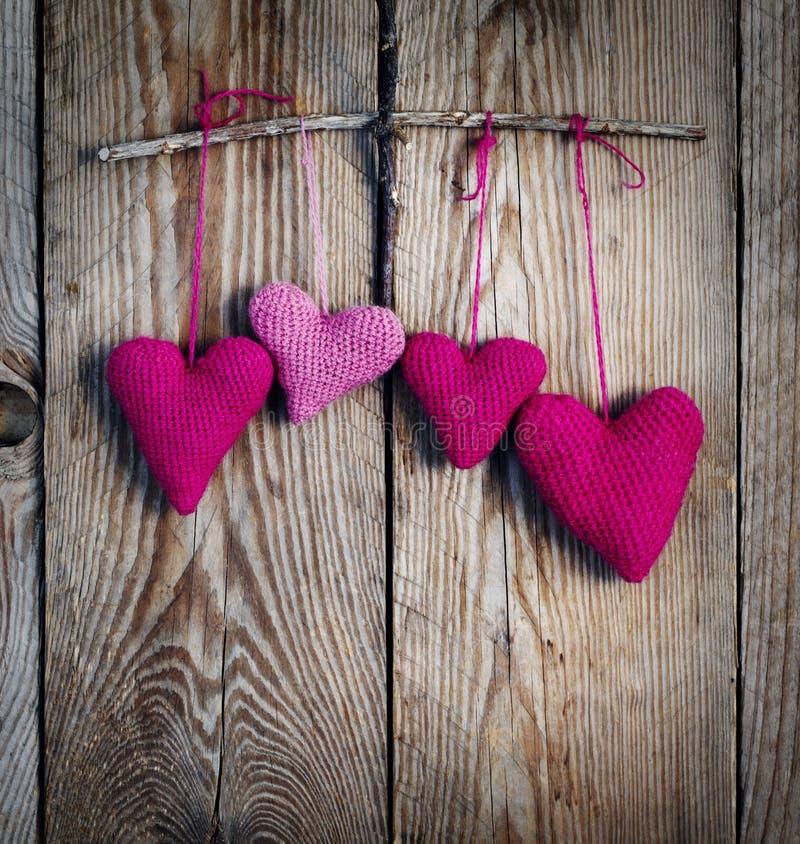 在木背景的钩针编织桃红色心脏 图库摄影
