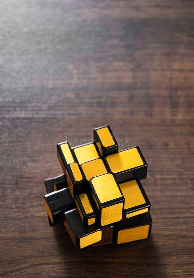 在木背景的镜子不可思议的立方体 图库摄影