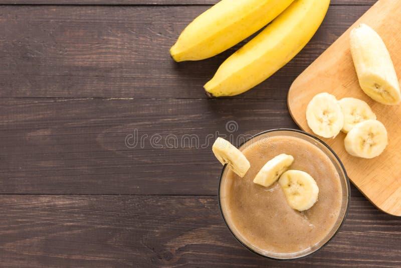 在木背景的香蕉圆滑的人 顶视图 免版税库存图片