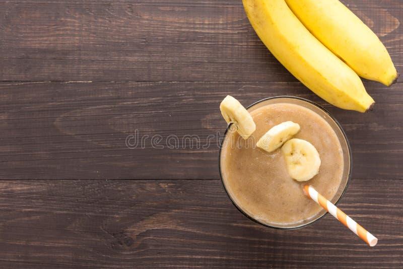 在木背景的香蕉圆滑的人 顶视图 免版税图库摄影