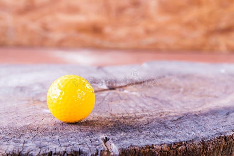 在木背景的黄色小小高尔夫球球 免版税库存照片