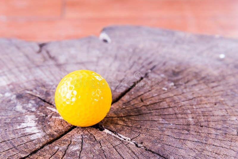 在木背景的黄色小小高尔夫球球 免版税库存图片