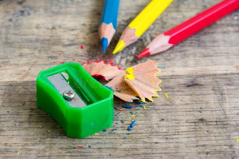 在木背景的绿色磨削器与原色铅笔 库存图片