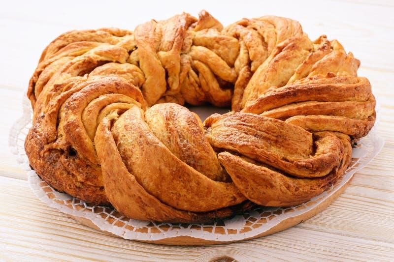 在木背景的结辨的桂皮卷蛋糕 免版税库存图片