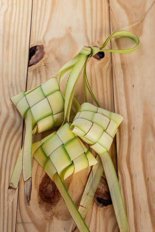 在木背景的Ketupat囊- Ketupat是由米做的饺子的类型被包装在一个菱形容器里面  库存图片