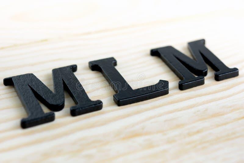 在木背景的MLM (或多级推销)信件 免版税图库摄影