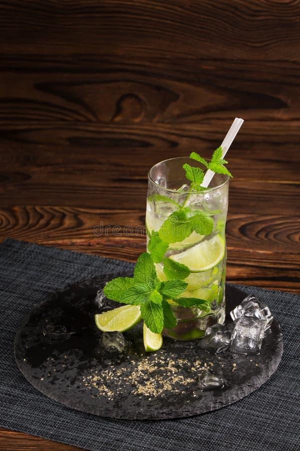 在木背景的Mojito鸡尾酒 与秸杆、薄荷叶和冰块的新鲜的石灰mojito 刷新的酒精 复制空间 免版税库存图片