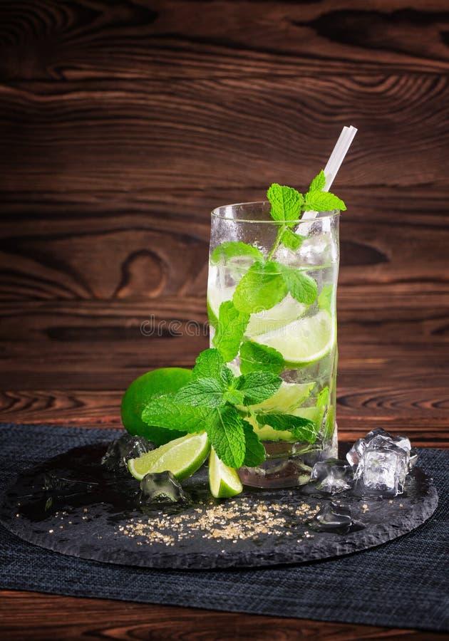 在木背景的Mojito鸡尾酒 与秸杆、薄荷叶和冰块的新鲜的石灰mojito 刷新的酒精 复制空间 库存图片