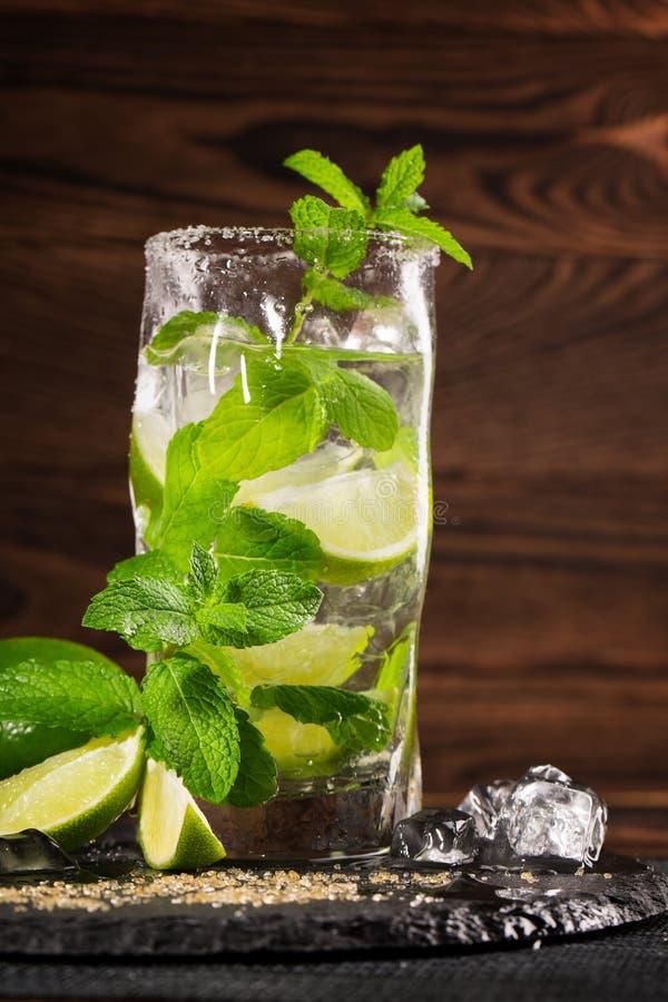 在木背景的Mojito鸡尾酒 新鲜的石灰、薄荷叶和冰块在一块透明玻璃 刷新的酒精饮料 库存照片