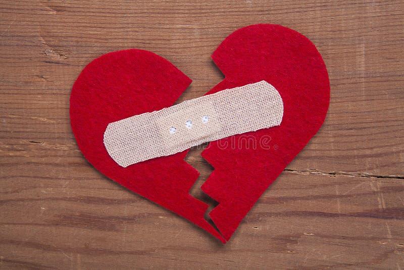 在木背景隔绝的微小的红色心脏标志 免版税库存图片
