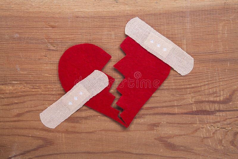 在木背景隔绝的残破的红色心脏标志 库存图片