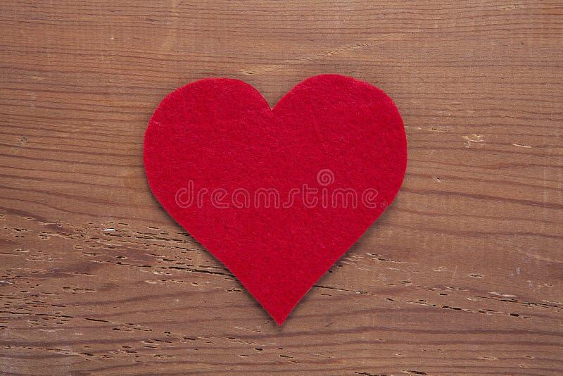 在木背景隔绝的红色心脏标志 库存图片