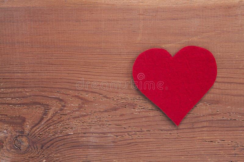 在木背景隔绝的红色心脏标志 免版税库存图片