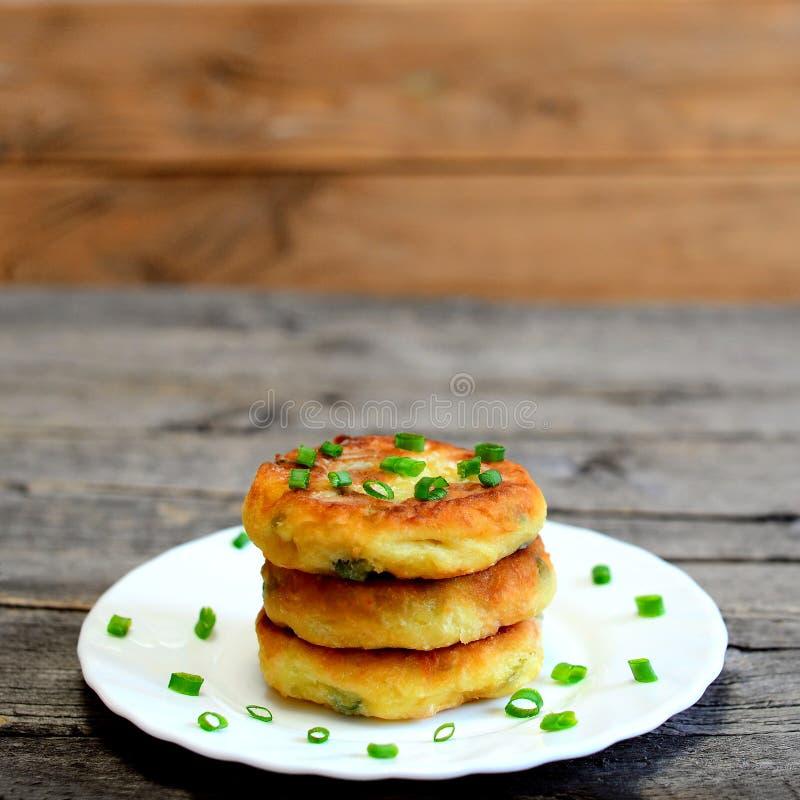 在木背景隔绝的板材的混杂的菜小馅饼 油煎的小馅饼烹调了土豆,绿豆,红萝卜 免版税库存图片