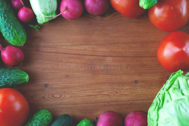 在木背景顶视图的平的被放置的生活方式新鲜蔬菜框架 库存图片