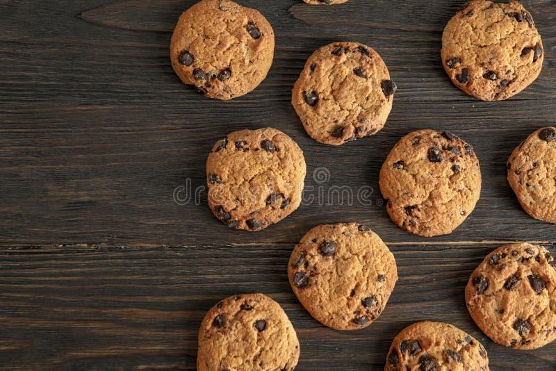 在木背景,平的位置的可口巧克力曲奇饼 免版税库存图片
