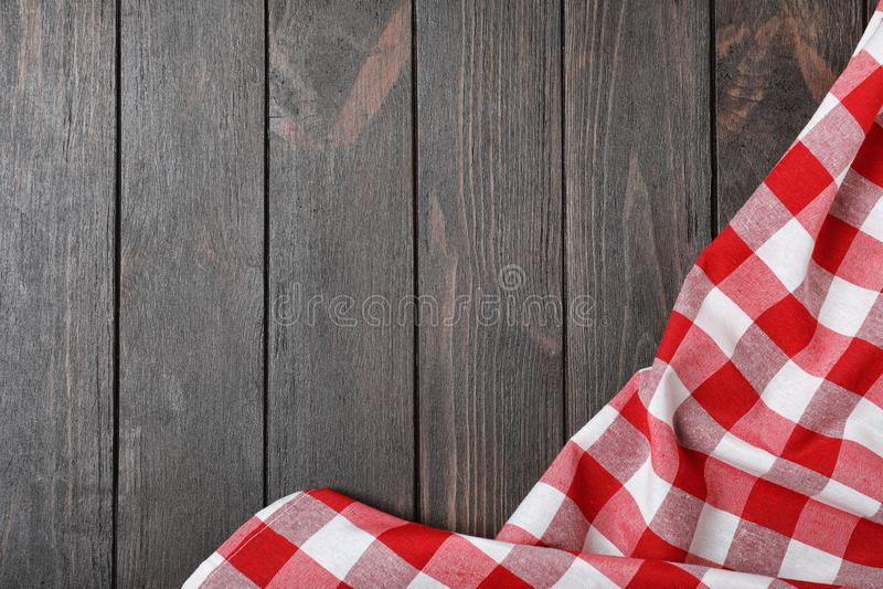 在木背景,顶视图的方格的野餐毯子 免版税库存图片
