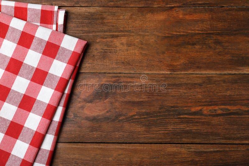 在木背景,顶视图的方格的野餐毯子 免版税库存照片