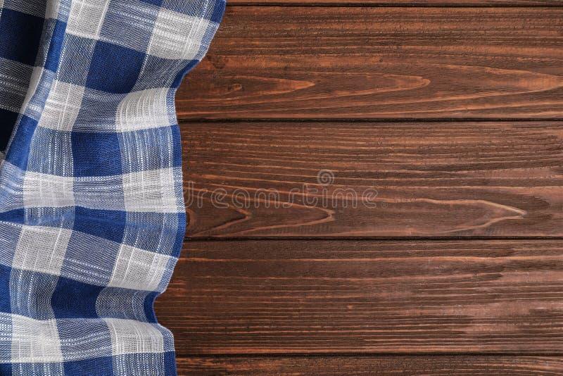在木背景,顶视图的蓝色格子花呢披肩洗碗布 免版税库存照片
