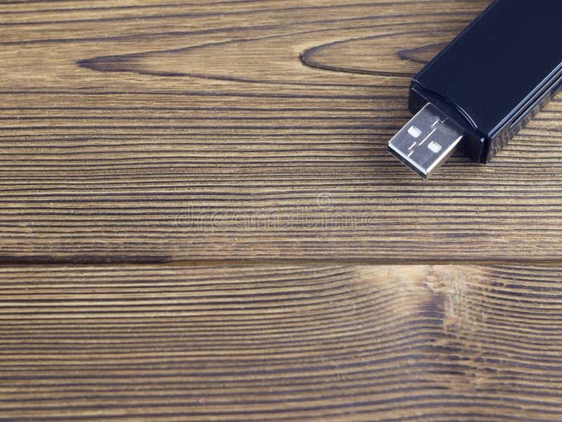 在木背景usb的黑USB闪光驱动 库存图片