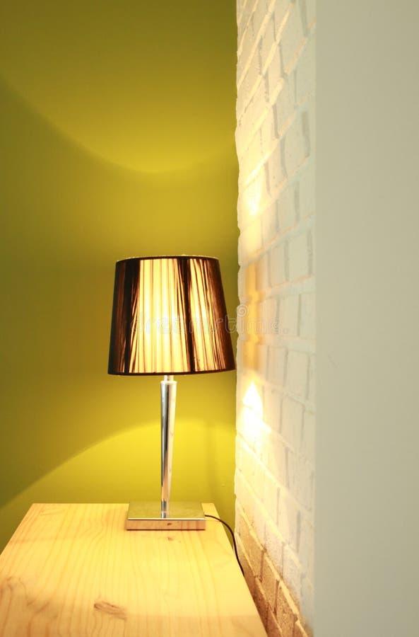 在木胸口的台灯在绿色墙壁和白色砖墙前面 免版税库存图片