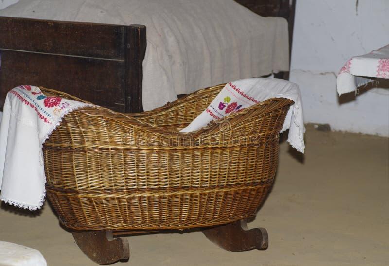 在木腿的一个小古色古香的木摇篮一个小婴孩的 免版税库存图片