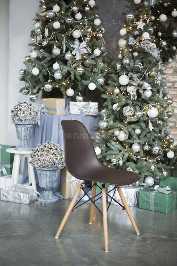 在木腿费用的棕色椅子在以装饰的绿色圣诞树锥体为背景的演播室在花瓶 免版税库存图片