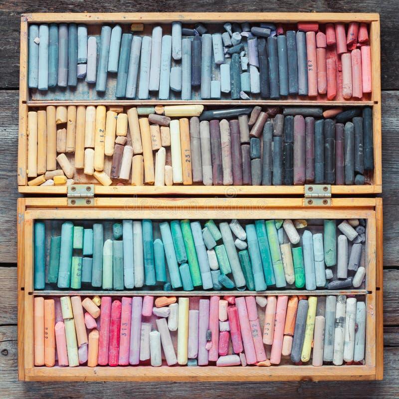 在木艺术家箱子的多彩多姿的淡色蜡笔在桌上 库存图片