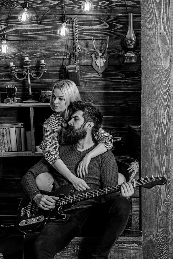 在木葡萄酒内部的夫妇享受吉他音乐 夫人和人有胡子的在梦想的面孔拥抱和戏剧吉他 免版税库存图片