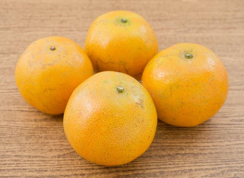 在木表上的四个新鲜的成熟和甜橙,桔子是柑橘种类的果子