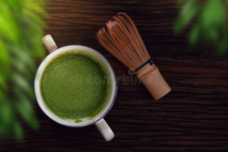 在木表上的热的Matcha绿茶拿铁杯与Chasen或竹飞奔 日本传统饮料 被弄脏的绿色叶子  库存图片