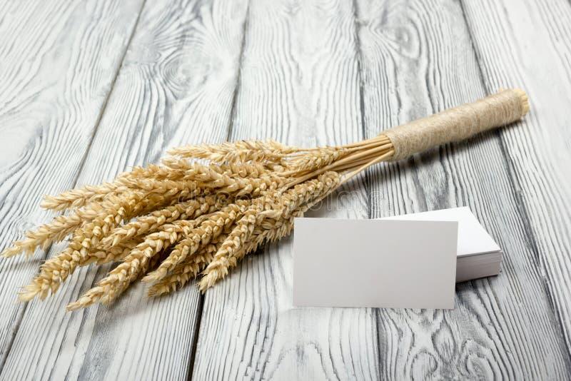 在木表上的麦子耳朵与空白的名片 捆在木背景的麦子 收获概念 图库摄影