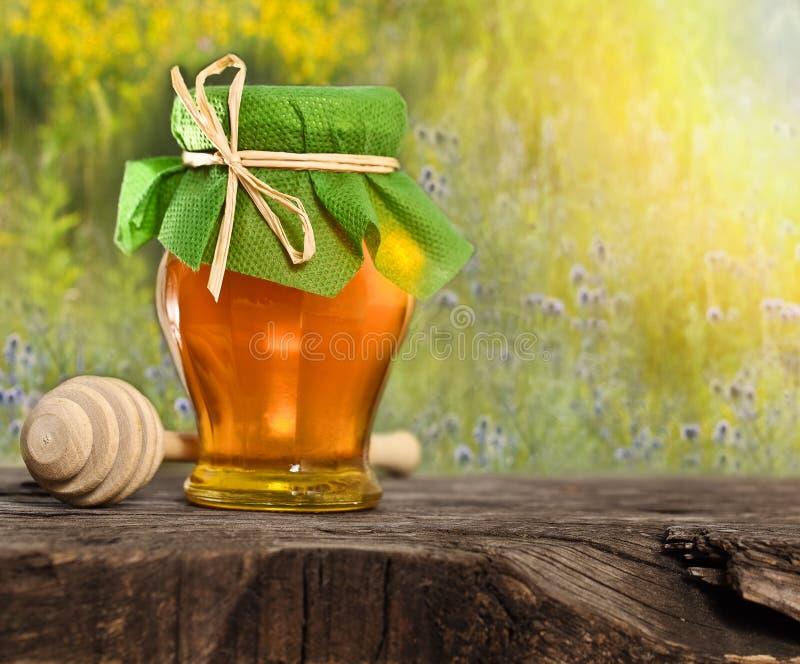 在木表的蜂蜜瓶子 库存图片
