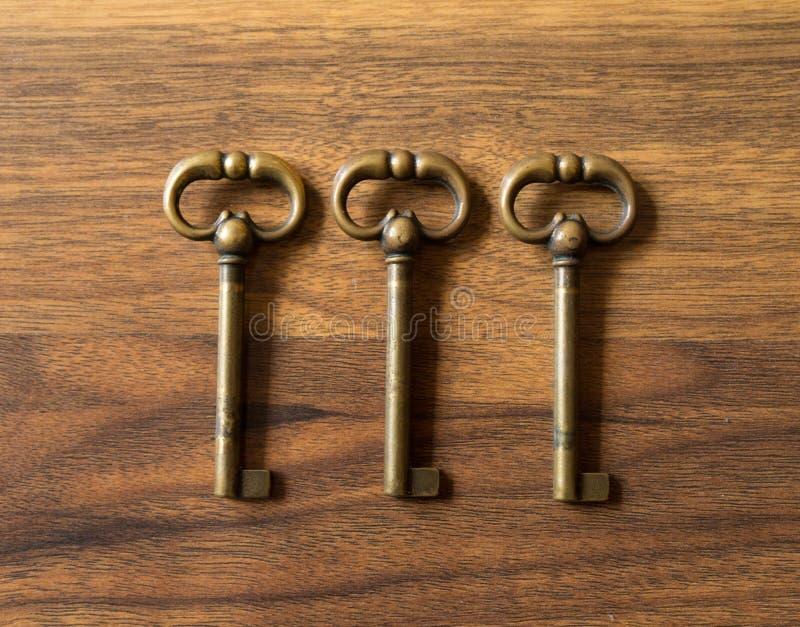 在木表面排列的三把古铜色钥匙 库存照片