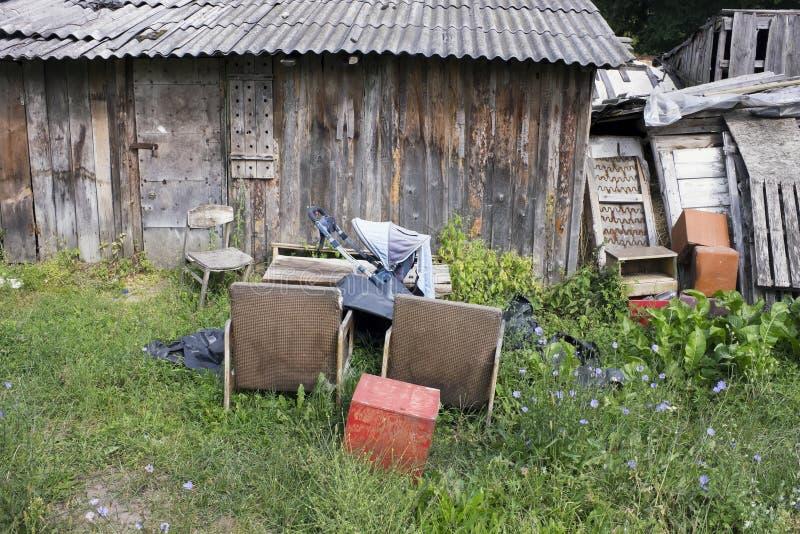 在木被毁坏的棚子附近的一个村庄垃圾堆 免版税库存图片