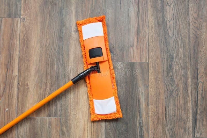 在木被碾压的地板上的现代拖把在家 清洁概念洗碗盘行为液体海绵 免版税库存图片